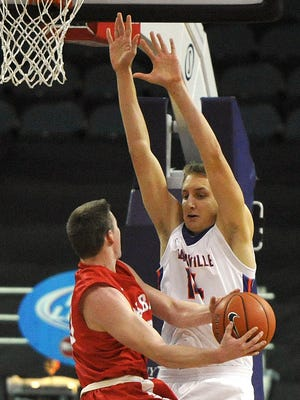 University of Evansville's Sergej Vucetic towers over Johnny Jager of Wabash College during the first half of a exhibition game at the Ford Center in Evansville.