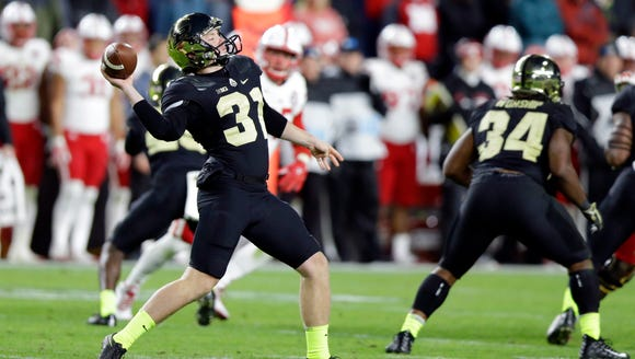 Purdue punter Joe Schopper (31) throws a pass on a