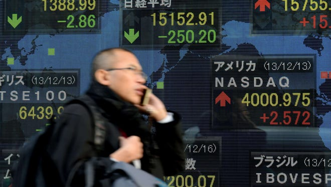 A man uses a mobile phone as he walks past an electric quotation board displaying the Nikkei key index of the Tokyo Stock Exchange on Dec. 16, 2013.
