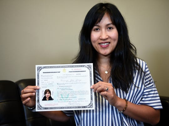 June George poses with her naturalization certificate