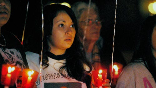 Xenia Mata holds a candle for her father, who passed away in 2003, during the 2014 Candlelight Vigil of Remembrance and Hope. This year's vigil will be held Saturday and will include a candlelight procession from United Methodist Church to Pioneer Park.