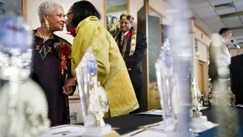 One of 2013's honorees, Juanita Kirkland, left, receives her award from Dr. Deborah McMillan amid the sparkles of other awards during the African/ African-American Love Feast and Recognition Dinner XIX.