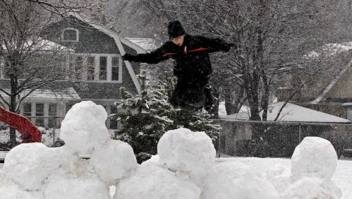 Danny Grennier, 10, from Milwaukee,  and a student at Wilson Elementary School in Wauwautosa, jumps off the snow fort he and  other neighborhood kids built on the playground after school during a winter snow storm.