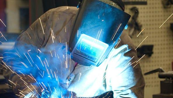 A Raymond Corp. employee in Greene, N.Y. welds the