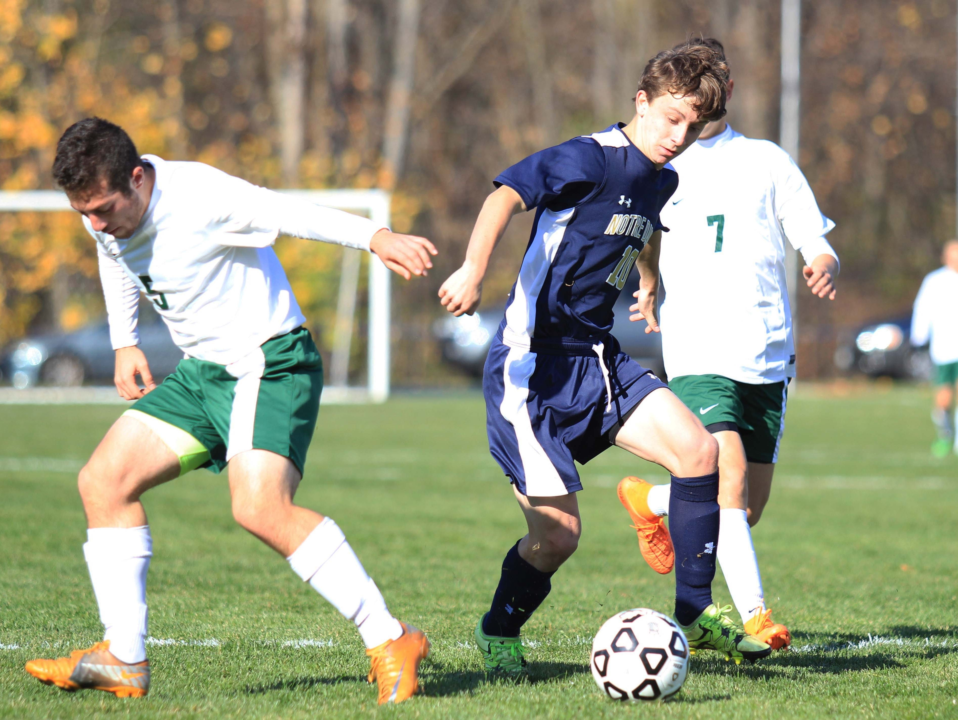 Notre Dame's Michael Woglom (center) battles defenders during the NYSPHSAA Class C final in Middletown.