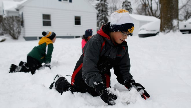 Ernesto Tabares, 11, tries to roll the base for a snowman without much luck as his sister, Gabriela, and cousin, Diego Tabares, play behind him Tuesday in Green Bay.