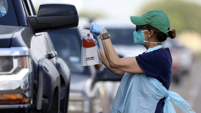 Health officials and members of the military assist during COVID-19 testing on July 8 at H-E-B Park in Edinburg.
