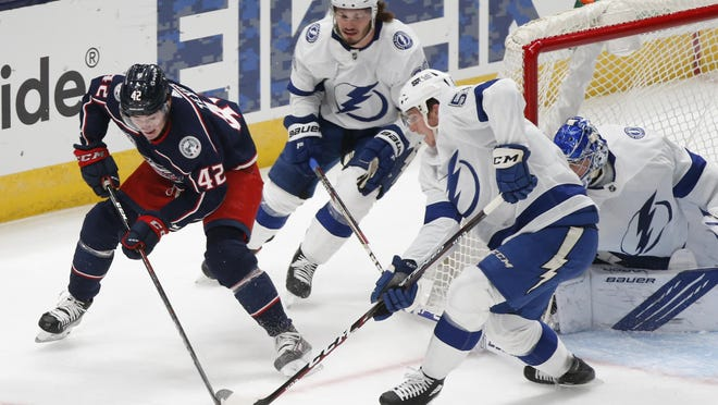 Columbus Blue Jackets' Alexandre Texier, left, of France, looks for an open shot as Tampa Bay Lightning's Mikhail Sergachev, center, of Russia, and Callan Foote defend during the first period of an NHL hockey game Saturday, Jan. 23, 2021, in Columbus, Ohio.
