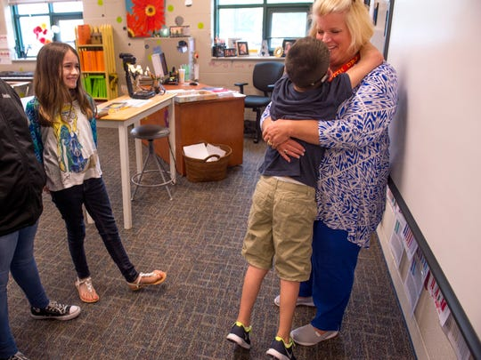 Kyle Watkins, 12, hugs his teacher, Annie Alcorn, after class as his classmate, Kim Abbey, 12, waits for him to go to lunch Thursday, April 27, 2017. Alcorn is a special education teacher at Castle South Middle School in Warrick County.