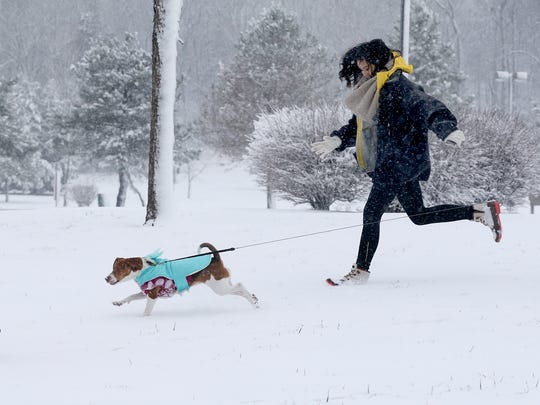Kelsie Hedge, left, and Destiny Luangrath, run with Lunangrath's beagle Emy in the snow at Barfield Crescent Park on Friday, Jan. 22, 2016, in Murfreesboro.