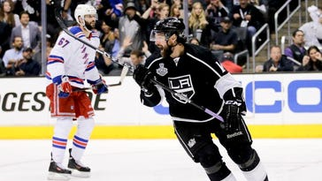 Los Angeles right wing Justin Williams (right) celebrates his game-winning goal as New York's Benoit Pouliot looks on in overtime of Game 1 of the Stanley Cup Finals on Wednesday in Los Angeles.
