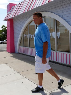 Simply Fabulicious owner Mark Houston walks outside his store on Wednesday in Farmington.