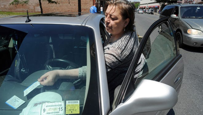 Hopewell Junction resident Valerie Menchen puts the parking meter receipt on the dashboard of her vehicle July 11 while parked on Main Street in the City of Poughkeepsie.