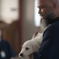 An inmate at Eastern Oregon Correctional Institution holds the puppy he'll help train through a new program Joys of Living Assistance Dogs launched at the prison.