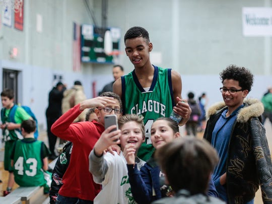 Students crowd around to take a selfie with Emoni Bates after a middle school game Feb. 3, 2017 at Clague Middle School in Ann Arbor.