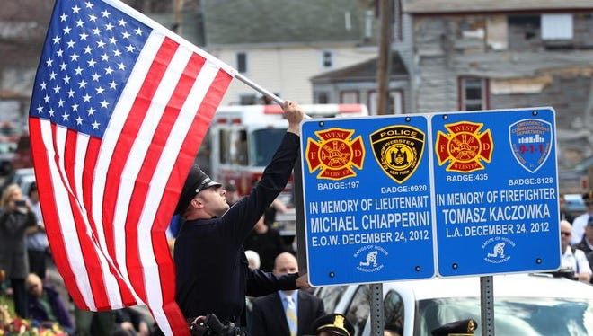 Rochester police officer Chris Kaltenbach places a flag during memorial sign ceremony on Lake Road in Webster where firefighters Mike Chiapperini and Tomasz Kaczowka were killed on Christmas Eve 2012. The Badge of Honor Association placed the sign in remembrance of them.