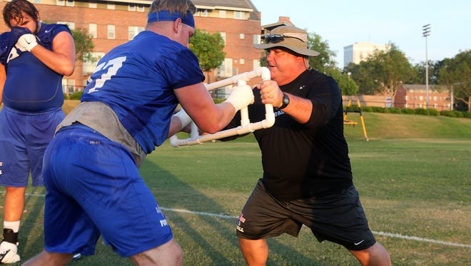 Louisiana Tech offensive line coach Robert McFarland works on a drill Monday with senior tackle Jens Danielsen