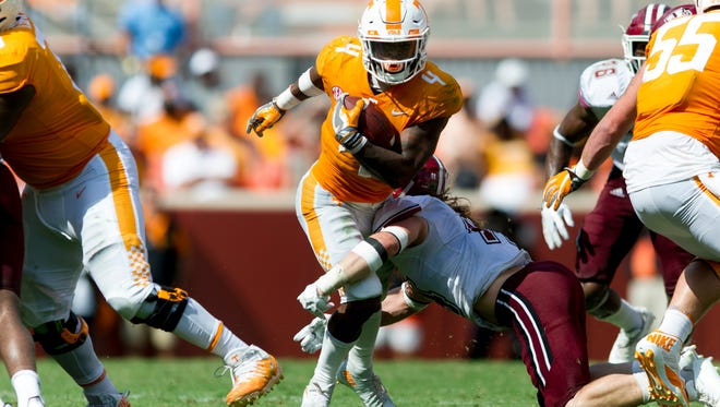 Tennessee running back John Kelly (4) runs the ball as UMass linebacker Bryton Barr (44) goes for a tackle during the Tennessee Volunteers vs. UMass Minutemen game at Neyland Stadium in Knoxville, Tennessee on Saturday, September 23, 2017.