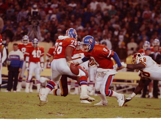 Denver Broncos quarterback Gary Kubiak (8) gets away from Washington Redskins linebacker Wilber Marshal (58) during a game on Nov. 20, 1989 at RFK Stadium in Washington.