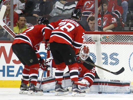 New Jersey Devils goalie Cory Schneider blocks a shot as teammates Kyle Quincey (22) and Damon Severson (28) help defend against the Edmonton Oilers during the second period of an NHL hockey game, Saturday, Jan. 7, 2017, in Newark, N.J. (AP Photo/Julio Cortez)