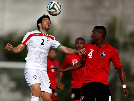 Iran's Khosrow Heidari, left, heads the ball while Trinidad and Tobago's Sheldon Bateau defends on the play during the first half of an international soccer friendly at the Corinthians soccer team training center Sao Paulo, Brazil, on Sunday, June 8, 2014. Iran will play in group F of the 2014 soccer World Cup. (AP Photo/Julio Cortez)