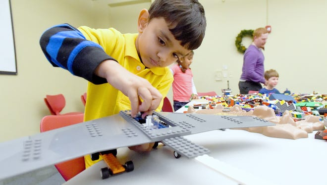 Om Madhani, 4, of Staunton fits one of the final Lego blocks needed to finish his creation. He scooped the piece from the large pile spread across several tables during LEGO mania! at Augusta Public Library in Fishersville on Tuesday, Jan. 3, 2017. The group meets the first and third Tuesdays of each month at 4:00 p.m.