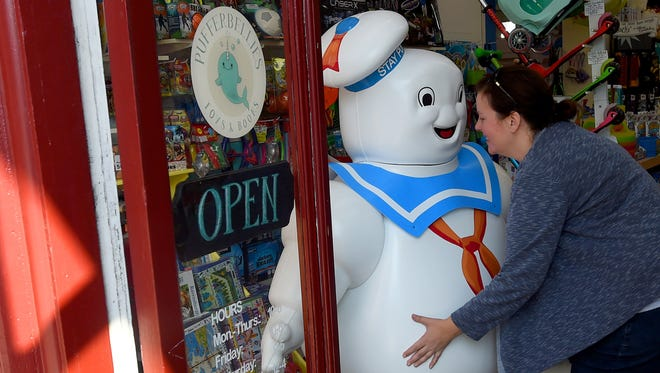Erin Blanton, co-owner of Pufferbellies, has her arms wrapped as far around the Stay Put Marshmallow Man as they will go. She carries him outside to place on the sidewalk in front of the toy store in downtown Staunton on Thursday, Aug. 31, 2017.