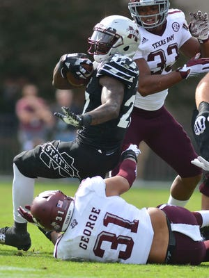 Mississippi State Bulldogs running back Aeris Williams (27) carries the ball defended by Texas A&M Aggies linebacker Claude George (31) at Davis Wade Stadium.