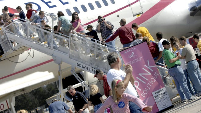 In this file photo, spectators lined up on the stairwell to tour the Delta Airlines jet take the opportunity to view the Pensacola Beach Air Show from a higher perspective. Global computer power outages have caused Delta flights to be cancelled or delayed. The Delta flights at Pensacola International Airport have only been delayed so far.  Katie King/kking@pnj.com