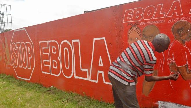 A  Liberian artist paints an Ebola-themed mural fin Monrovia.