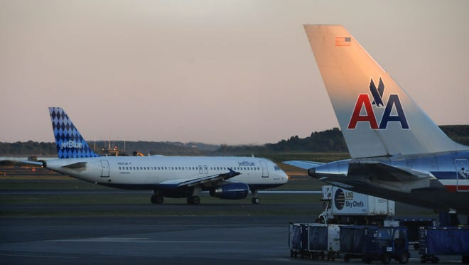 A JetBlue Airbus A320 taxis within view of an American Airlines aircraft at Boston Logan International Airport on Aug. 24, 2013.