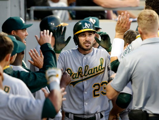 Oakland Athletics' Matt Joyce (23) celebrates in the dugout after his home run off Chicago White Sox starting pitcher Mike Pelfrey during the fifth inning of a baseball game Friday, June 23, 2017, in Chicago. (AP Photo/Charles Rex Arbogast)