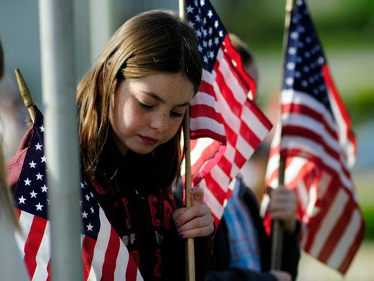 A young girl places a flag during a Prospect Hill Cemetery
