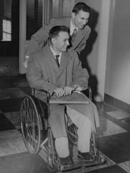 In this photo provided by the Herrick family, Ron Herrick pushes his twin brother, Richard, in a wheelchair, Jan. 30, 1955, as they leave Peter Bent Brigham Hospital in Boston, Mass., following the first successful organ transplant. Ron donated a kidney to Richard who suffered from chronic nephritis, an inflammation of the kidneys. (AP Photo)