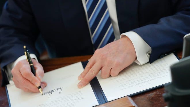 President Trump signs an executive order in the Oval Office on Feb. 9, 2017. Trump signed three executive orders related to reducing crime.