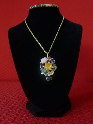 """The 2017 auction showpiece, called """"Around the World,"""" is a gemstone charm and chain designed by G. Alan's Fine Jewelry and Coin. It is valued at more than $5,000."""