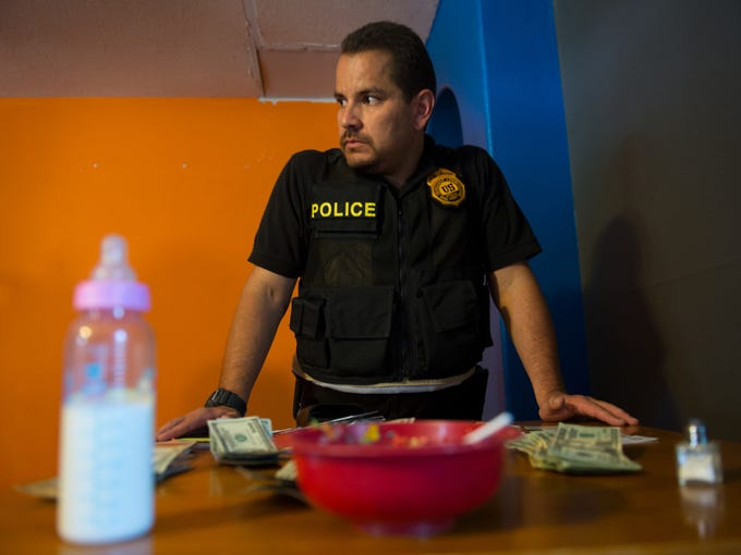 Eduardo Chavez, group supervisor of the Drug Enforcement Administration's district office in Albuquerque logs and bags evidence -- including nearly $1,200 in cash -- during a warrant search of the home of suspect Vito Gurule, 33.