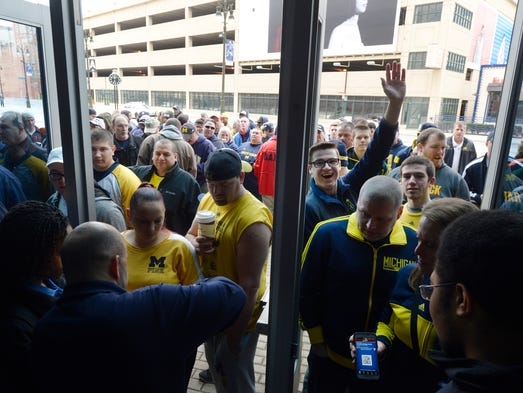 Crowds gather and begin enter Ford Field to watch University