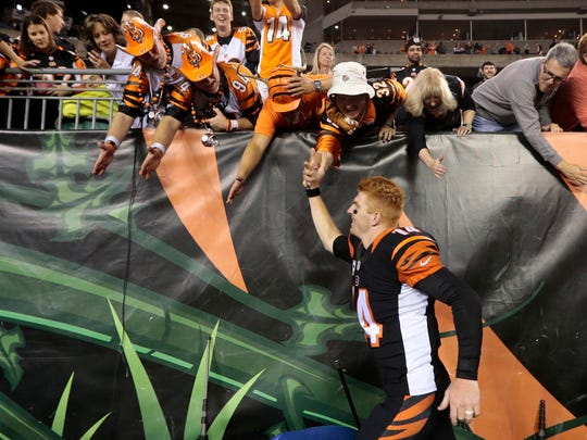 Cincinnati Bengals quarterback Andy Dalton (14) high fives fans as he runs for the locker room in the fourth quarter of the NFL Week 9 game between the Cincinnati Bengals and the Cleveland Browns at Paul Brown Stadium in downtown Cincinnati on Thursday, Nov. 5, 2015. The Bengals improved to 8-0 for the first time in franchise history with a 31-10 victory over Cleveland in the Battle of Ohio game.