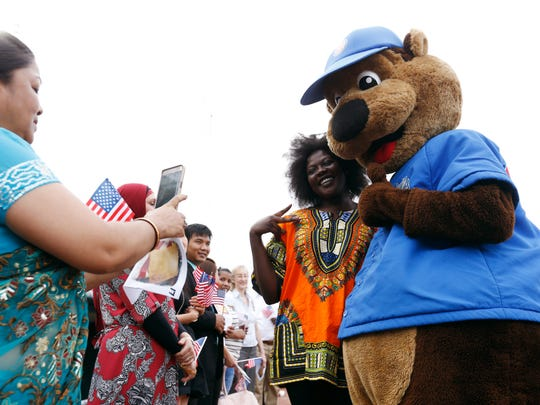 Athyang Koj of Des Moines, originally from South Sudan, gets her photo taken with Cubbie Bear before the annual Fourth of July naturalization ceremony at Principal Park in 2016.
