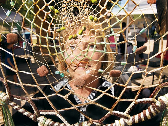 Nancy Baer peers through an intricate web embedded with semi-precious stones and other items at her Contemporay Dream Catchers booth at the Las Cruces Farmers' and Crafts Market.