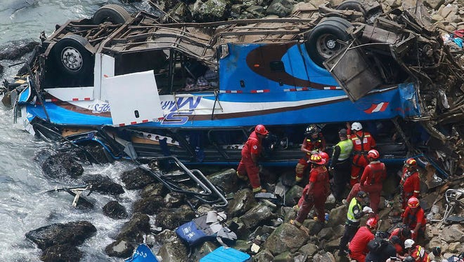 In this photo provided by the government news agency Andina, firefighters recover bodies from a bus that fell off a cliff after it was hit by a tractor-trailer rig in Pasamayo, Peru, on Jan 2, 2018.