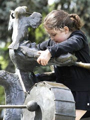 """Melissa Barrios plays on the """"Parade of Animals"""" sculptures in Willson Park."""