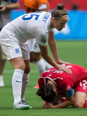 England's Casey Stoney, left, consoles Canada's Christine Sinclair after England's 2-1 win during a quarterfinal of the Women's World Cup soccer tournament, Saturday, June 27, 2015, in Vancouver, British Columbia, Canada.