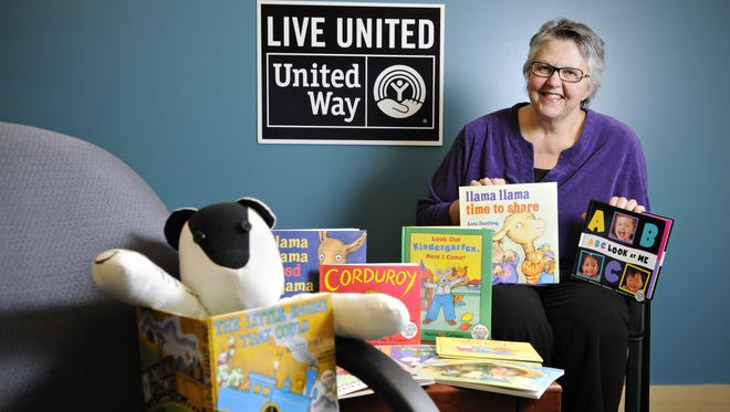 """Betty Schnettler, the namesake of """"Betty's Books,"""" shows some of the books provided free monthly for children from birth to age 5 through the Imagination Library."""