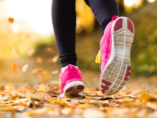 Close up of runner's feet running in autumn leaves