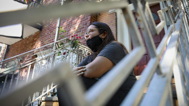 "Natalia Afonso, 27, an international student from Brazil at Brooklyn College, sit on a stoop outside her home during an interview, Thursday July 9, 2020, in New York.  Afonso, who is studying teaching education and finished her first semester this spring, said she has lived in the U.S. for 7 years and ""I don't see myself moving back to Brazil at this point."