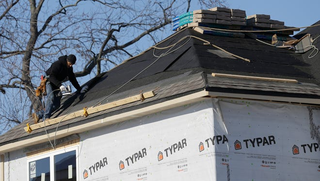 A construction worker builds a new home in Wilmette, Ill. in December.