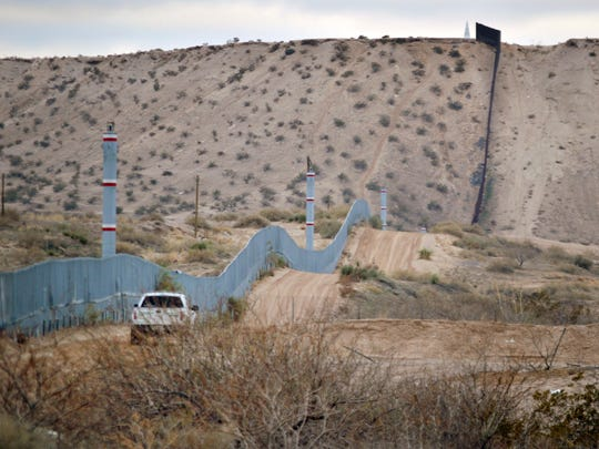 In this Jan. 4, 2016 photo, a U.S. Border Patrol agent drives near the U.S.-Mexico border fence in Sunland Park, N.M.
