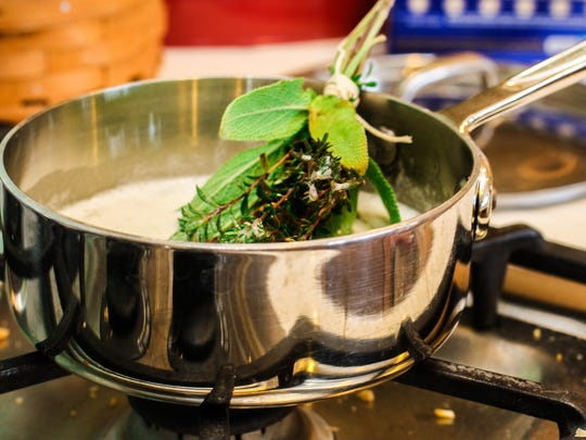 A bundle of herbs tied into a brush is dipped in butter and used to baste smoked turkey during cooking.